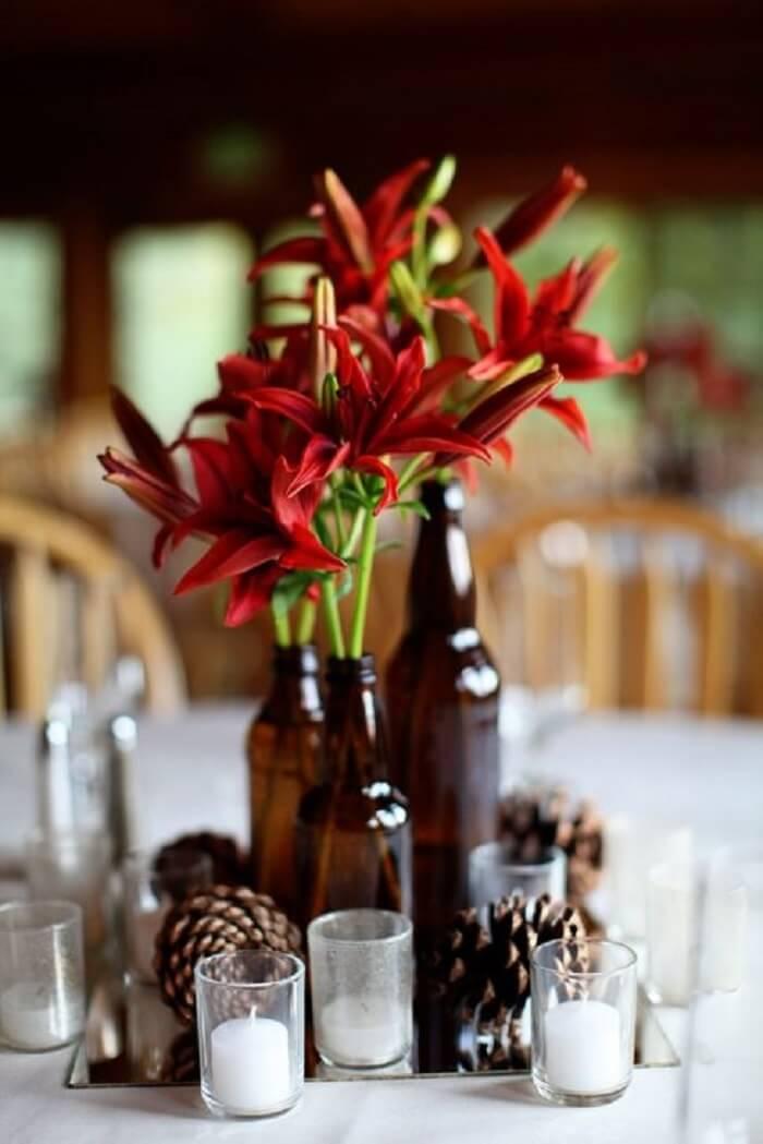 Decoração do centro de mesa para festa Chá Bar feita com garrafas de vidro e flores