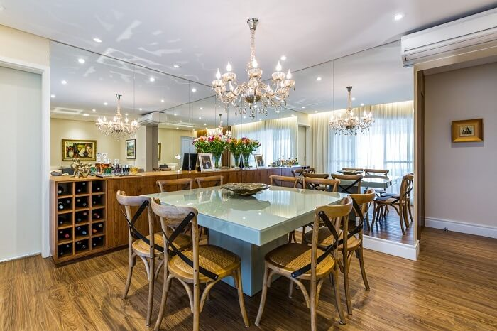 Sala de jantar com adega, parede de espelho e lustre