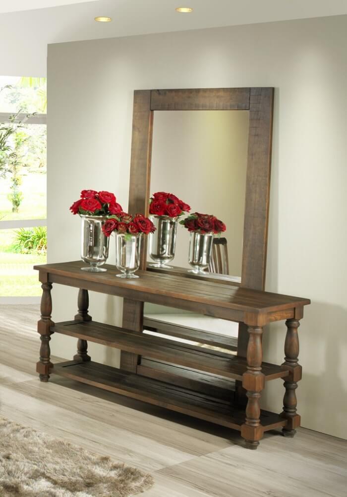 Moldura para espelho grande feito em madeira posicionado atrás do aparador