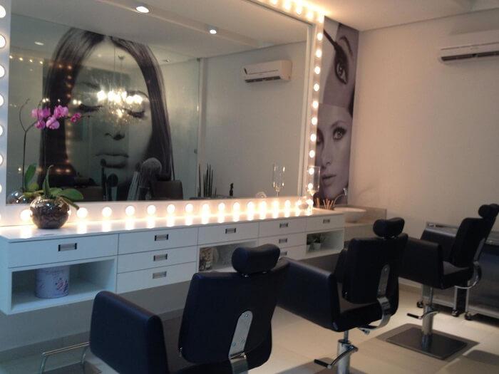 Moldura para espelho iluminada e cadeiras pretas encantam a decoração do camarim