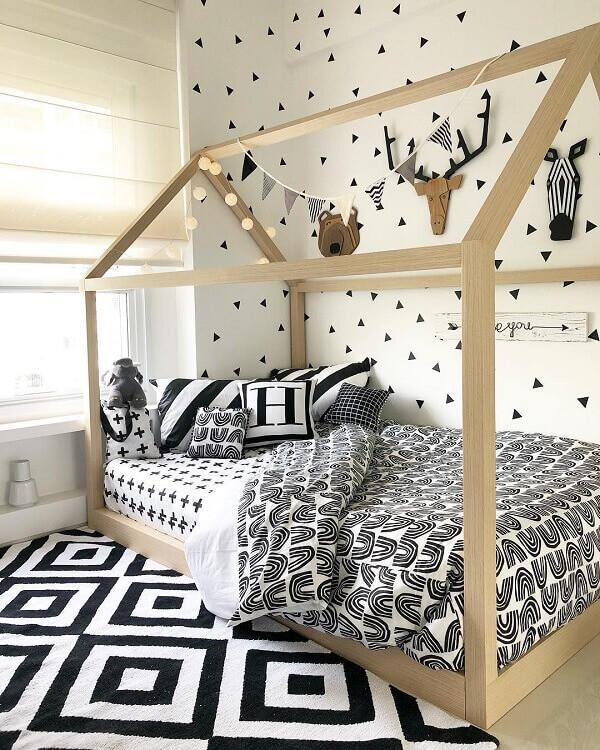 Muito aconchego e conforto para esse quarto com cama casinha e tapete preto e branc