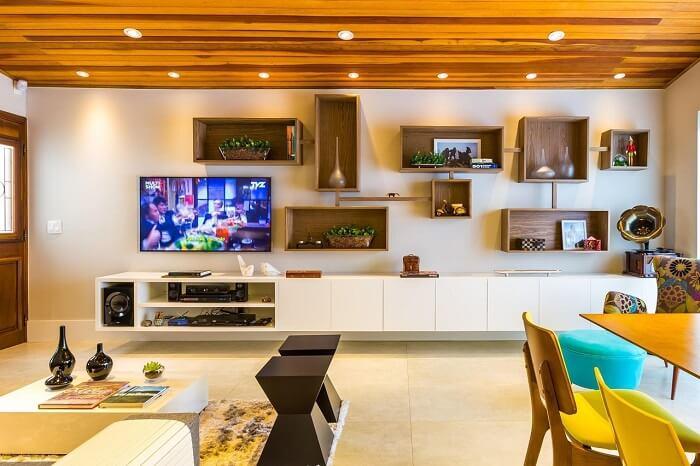O rack suspenso branco ocupa grande parte da parede da sala de estar. Projeto de BY Arq&Design