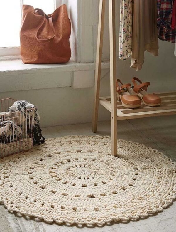 O tapete de crochê redondo complementa a decoração do ambiente e serve de conforto aos pés