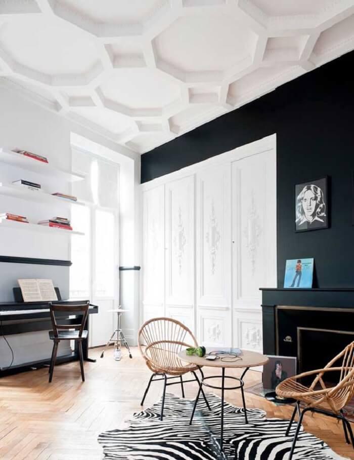 O teto feito com placa de gesso 3D se contrasta com as paredes em tom preto