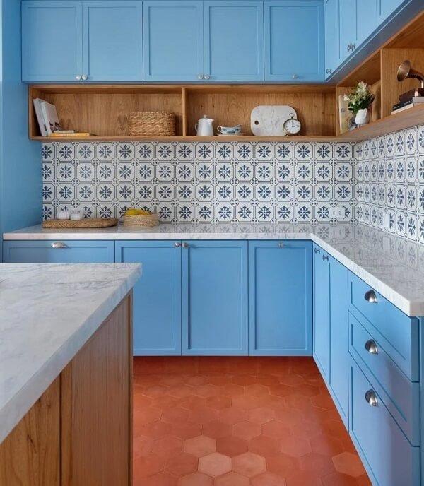 Os nichos de madeira na cozinha ajudam na organização dos livros de receitas