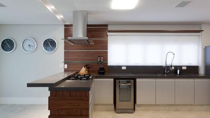 O relógio de parede complementa a decoração da cozinha ampla