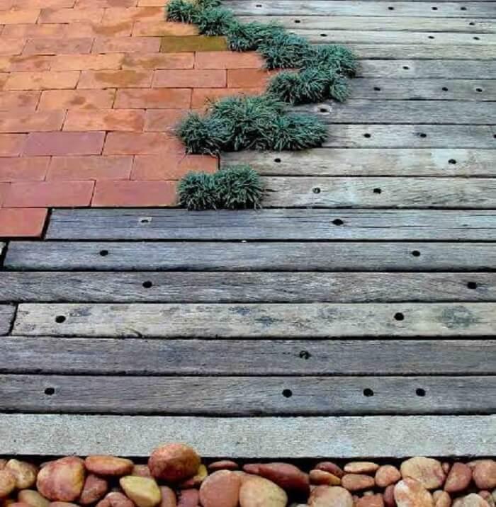 Piso externo feito de cruzeta, tijolo, pedra e grama preta