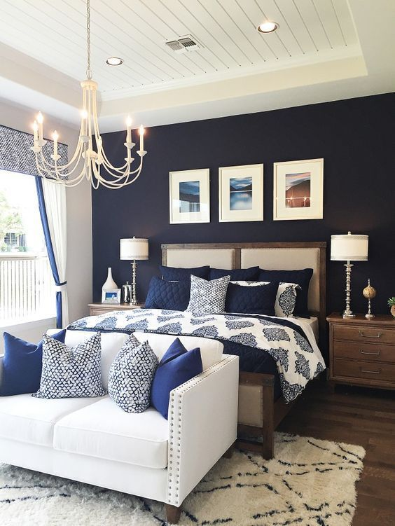 Quarto com parede azul marinho e enfeites modernos