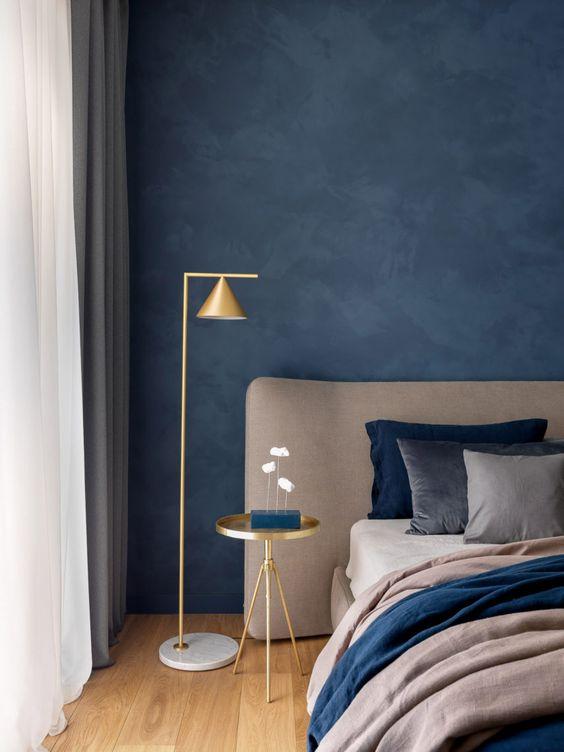 Quarto com parede cor azul marinho com lustre dourado