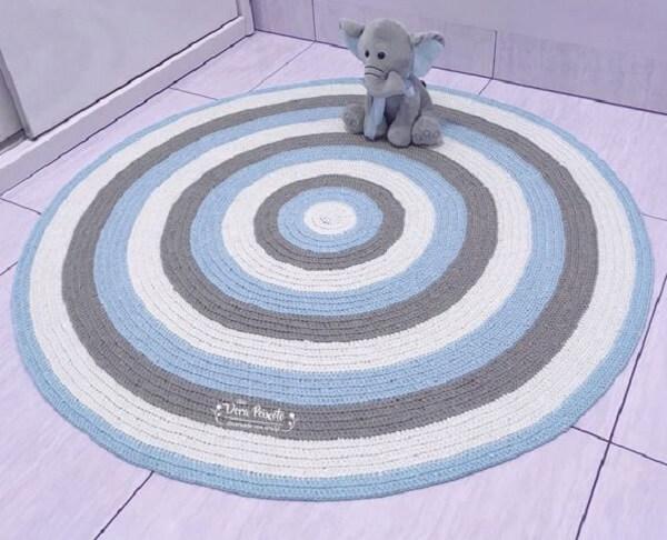 Quarto de bebê com tapete de crochê redondo colorido e móveis em tom branco
