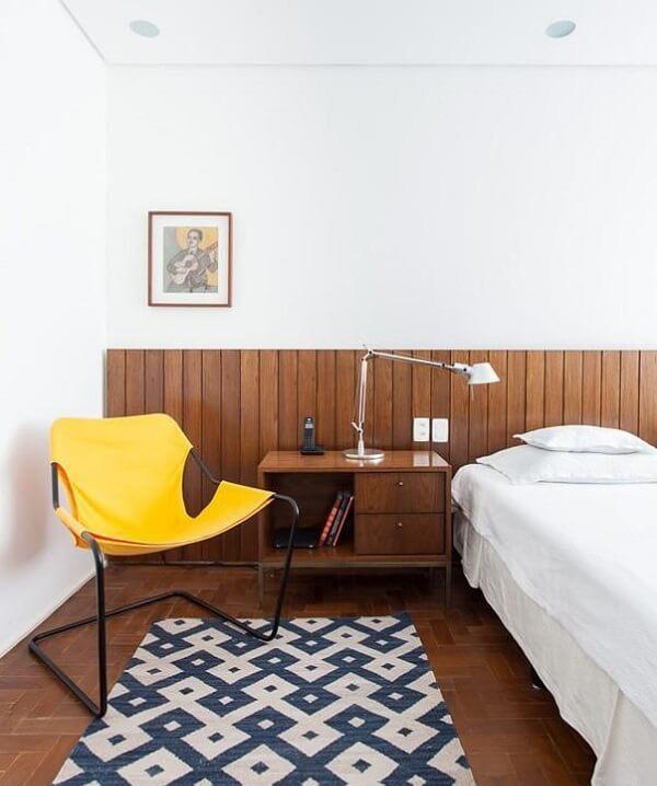 Quarto de casal com cadeira amarela posicionada ao lado da cama