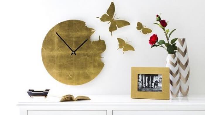Relógio de parede em tom dourado com borboletas