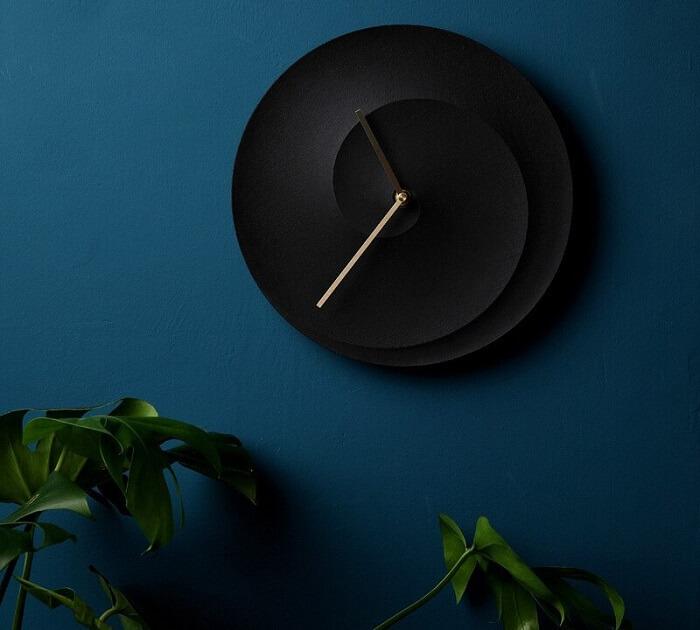 Relógio de parede feito de concreto e pintado de preto