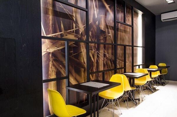 Restaurante com mesa preta e cadeira amarela