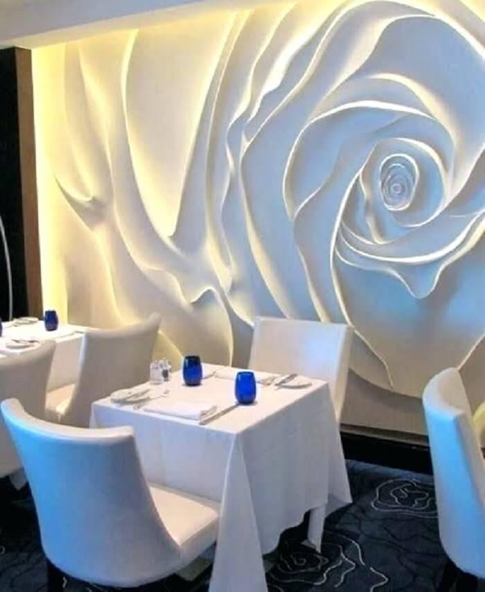 Restaurante com parede revestida com placa de gesso 3D em formato de rosa