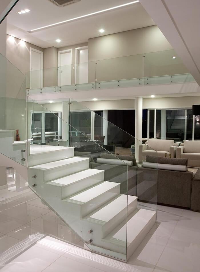 Sala com escada branca e guarda corpo de vidro temperado