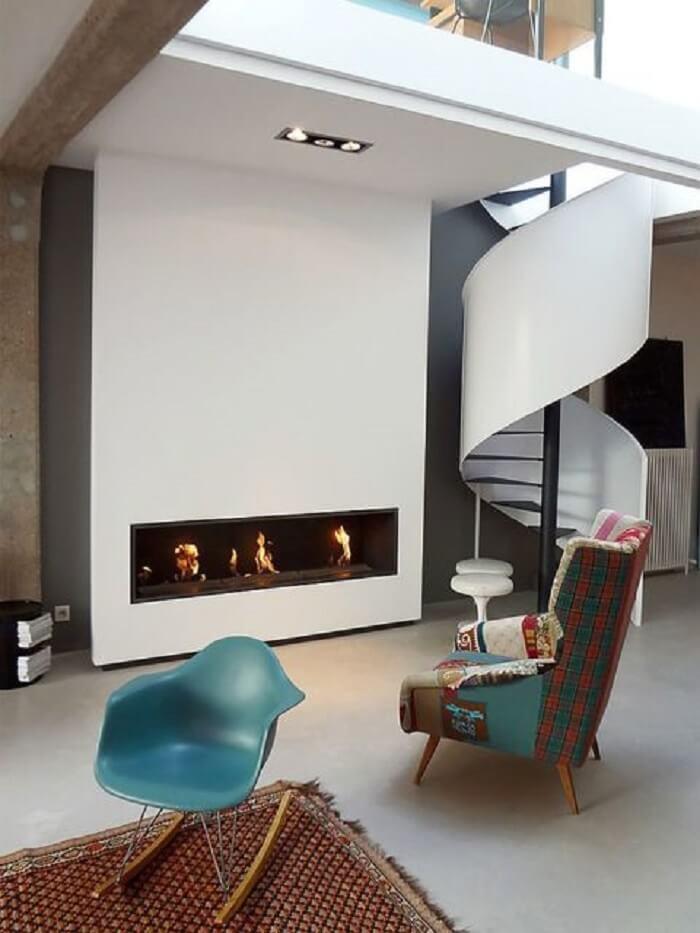 Sala com escada caracol branca e poltronas coloridas