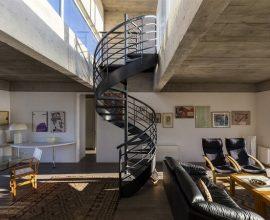 Sala com escada caracol em tom preto se destaca na decoração