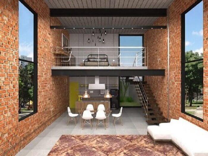 Sala com escada, cozinha americana, janelas amplas e parede de tijolinhos