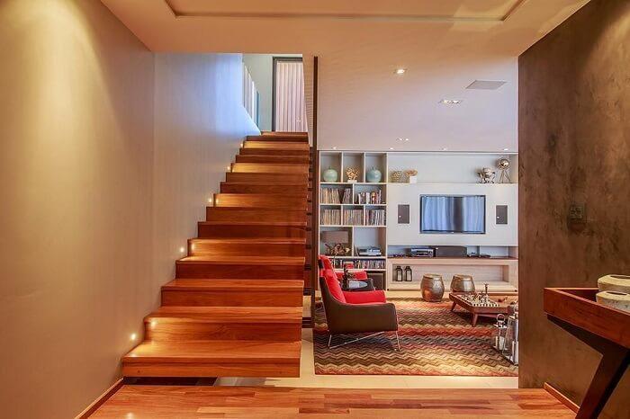Sala com escada de canto conta com lâmpadas pontuais nos degraus
