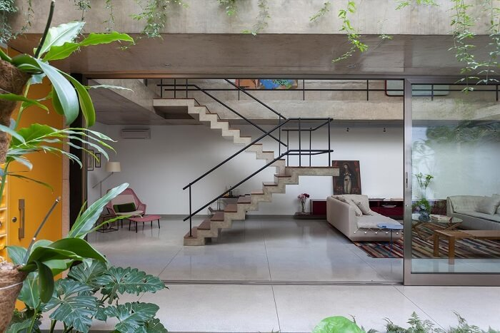 Sala com escada de concreto e corrimão de ferro