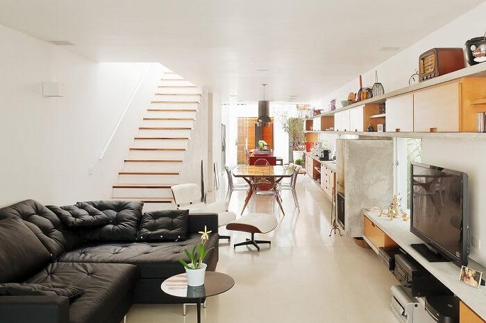 Sala com escada e cozinha americana se harmonizam na decoração