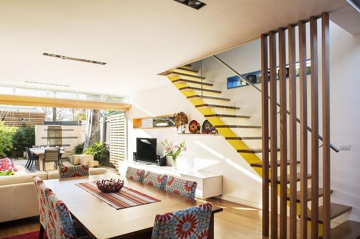 Sala com escada flutuante de madeira e guarda corpo de vidro
