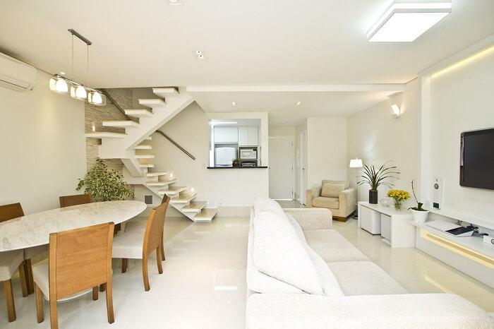 Sala com escada flutuante e cozinha americana