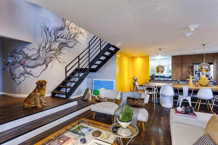 Sala com escada metálica encanta a decoração deste apartamento moderno