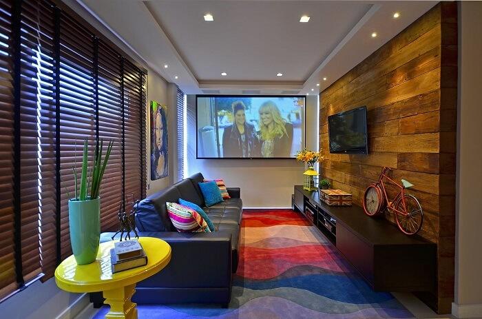 Sala de TV com tapete colorido e rack preto suspenso. Projeto de Juliana Baumhardt