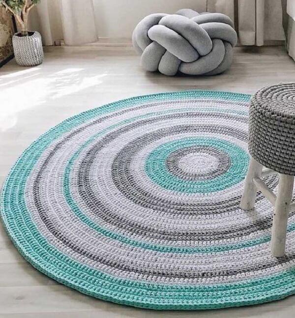 Sala de estar clean com tapete de crochê redondo colorido