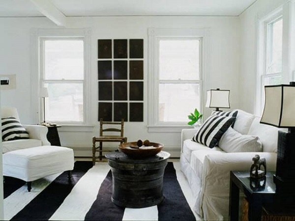Sala de estar clena com tapete preto e branco listrado