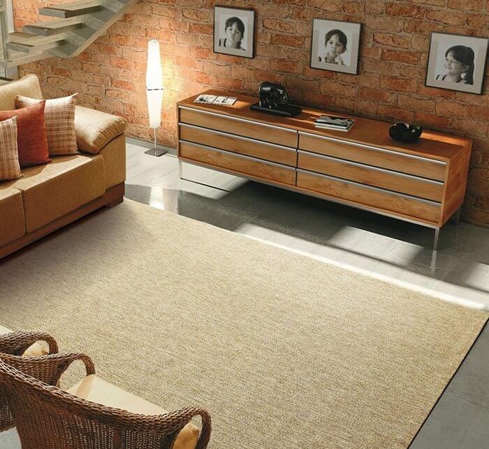 Sala de estar com parede de tijolinhos e tapete sisal