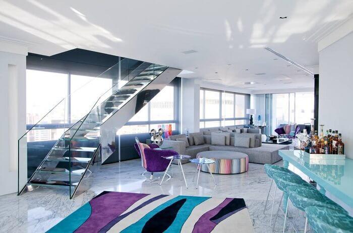 Sala de estar com escada de vidro favorece a entrada de luz natural no espaço