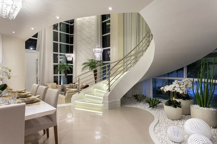Sala de estar com escada deslumbrante conta com jardim de inverno