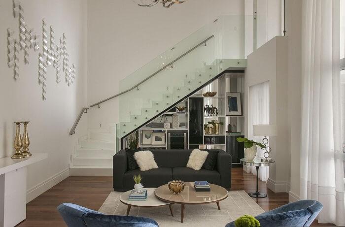 Sala de estar com escada flutuante e guarda corpo de vidro temperado