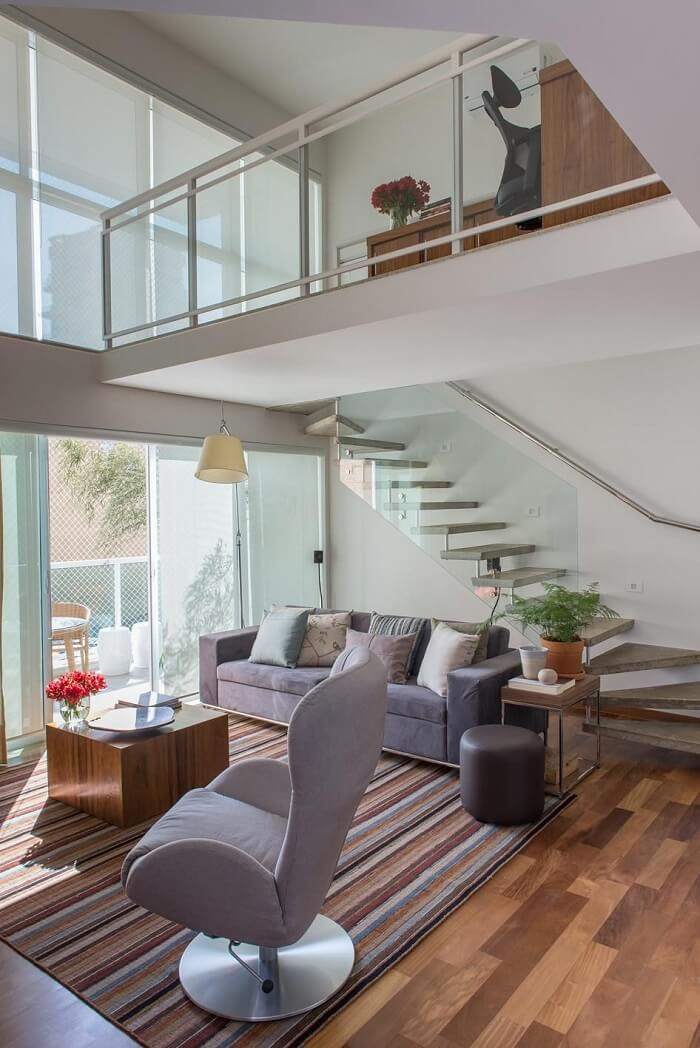 Sala de estar com escada flutuante e guarda corpo de vidro