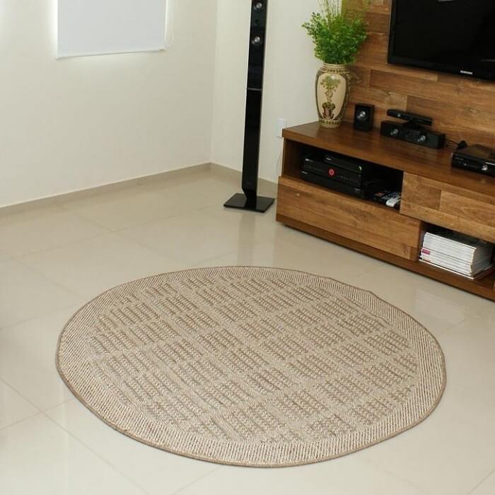 Sala de estar com painel de tv feito em madeira e tapete sisal