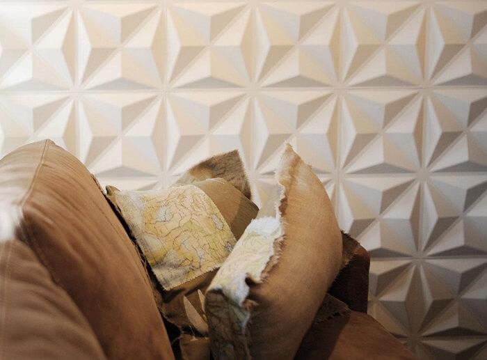 Sala de estar com parede revestida com placa de gesso 3D com desenho triangular