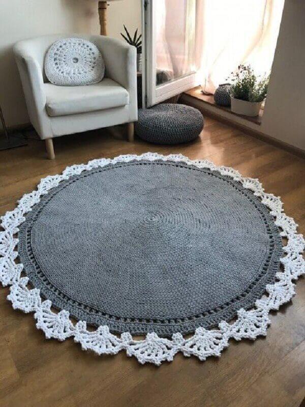 Sala de estar com poltrona e tapete de crochê redondo em tom branco e cinza