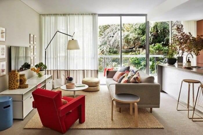 Sala de estar gourmet com poltrona vermelha e tapete sisal