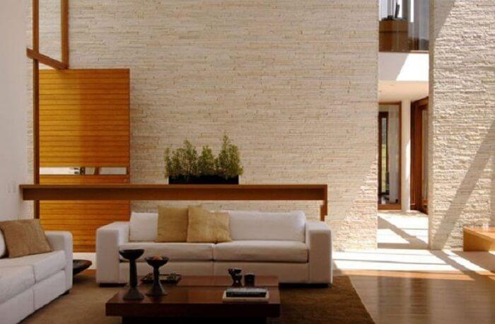 Sala de estar neutra com parede revestida com pedra São Tomé