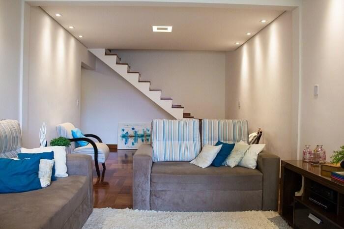 Sala de estar pequena com escada rente a parede