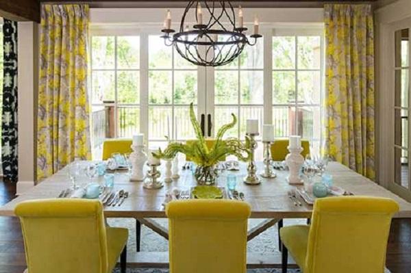 Sala de jantar com cadeira amarela estofada e mesa de madeira