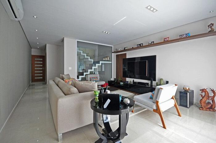 Sala pequena com escada e parede de vidro