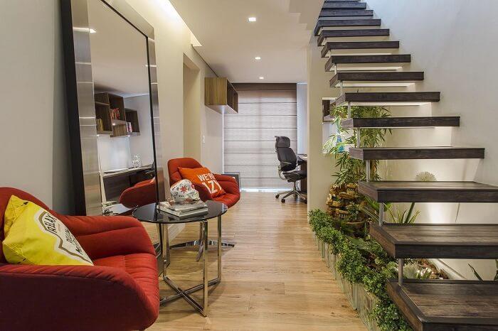 Sala pequena com escada flutuante conta com jardim de inverno em seu interior