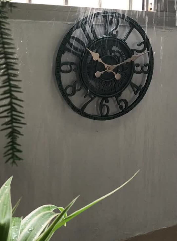 Relógio de parede preto com ponteiros em dourado