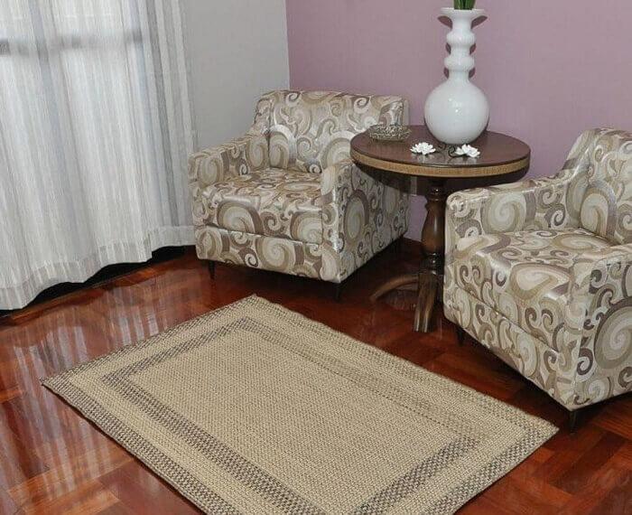 Tapete sisal retangular foi posicionado em frente as poltronas da sala de estar