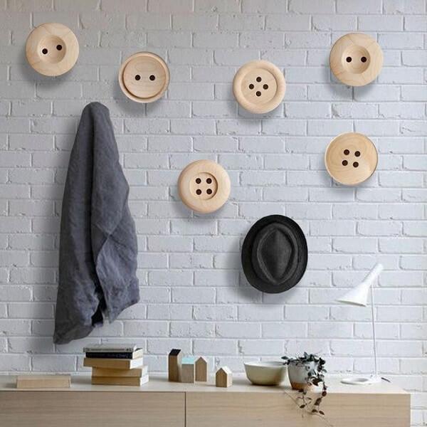 Gancho de parede em formato de botões encanta a decoração deste ambiente