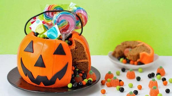 Bolo de Halloween em formato de abóbora serve de suporte para doces